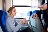 Young+woman+traveling+by+train%2C+having+her+ticket+checked+by+the+train+conductor