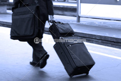 Businessman pulling a trolley at station